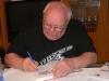 podpisuje knihu